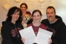 SIC graduate Madeline Rogers, center, proudly displays her letter of acceptance to Southern Illinois University's music program and the university's offer of a full-ride scholarship.  Rogers, 16, is surrounded by her mother, Lucinda; her sister, Lydia; dog Scruffy; and her father, Keith.