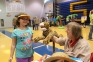 Harrisburg librarian, Kae McCue, chats with Lora Forster, age 7, from Eldorado, as Lora meets a friendly cheetah at the SIC Kids' Fair Safari.